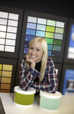 Happy female in hardware shop. Smiling woman in hard ware shop in front of color scale royalty free stock image