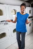 Happy Female Helper Gesturing In Laundry Royalty Free Stock Photos