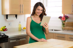 Happy female on her watching videos on her tablet computer while relaxing at home with perfect smile stock images
