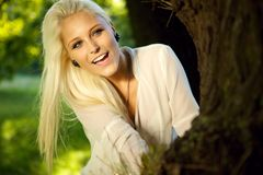 Happy female hiding behind a tree. Happy female playing hide and seek. Hiding behind a big tree Stock Photography