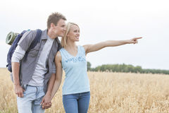 Happy female hiker showing something to man on field against clear sky Stock Photo