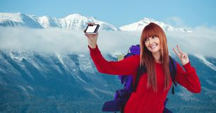 Happy female hiker taking selfie through smart phone against snow covered mountain Royalty Free Stock Photography