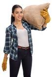 Happy female holding burlap sack on her shoulder Stock Photo