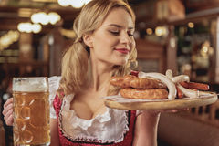 Happy female holding sausages and beer glass Royalty Free Stock Image