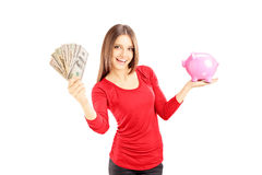 Happy female holding US dollars and pink piggy bank Royalty Free Stock Photography