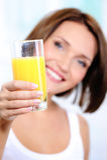 Happy female holds a glass of orange juice Stock Image