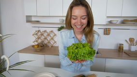 Happy female housewife takes bunch of salad leaves in hands and poses with smile at camera, standing in middle of. Nice young girl holds fresh green lettuce stock footage