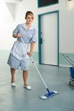 Happy female janitor holding mop Royalty Free Stock Image