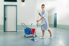 Happy female janitor holding mop Stock Photography