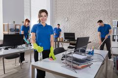Happy Female Janitor In Office Royalty Free Stock Images