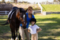 Happy female jockey with sister standing by horse. On field at paddock Stock Images