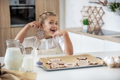 Happy female kid having fun with holiday sweet pasty. Look at me. Portrait of joyful girl is holding Christmas decorative cookie near ear as earring. She is Stock Photography