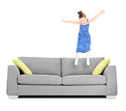 Happy female kid jumping on couch. Isolated on white background shot with tilt and shift lens Stock Images