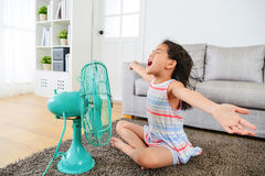 Happy female kid opening arms enjoying cool wind. Pretty happy female kid opening arms enjoying cool wind from electric fan and sitting on floor in living room Royalty Free Stock Images