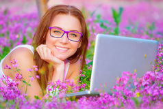 Happy female with laptop outside Stock Image