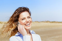 Happy female laughing on the smart phone Stock Photos