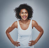Happy female leaning forward with hands on hips Royalty Free Stock Images