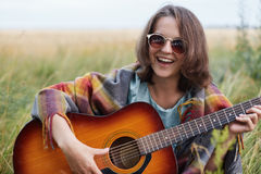 Happy female learning playing guitar while sitting at greenland having fun. Beautiful woman wearing sunglasses having good mood wh Royalty Free Stock Image