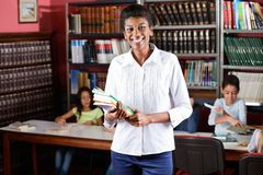Happy Female Librarian Holding Books While. Portrait of happy female librarian holding books while standing in library with students studying in background Royalty Free Stock Photography