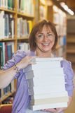 Happy female librarian holding a pile of books in a library Stock Photo