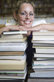 Happy Female Librarian Leaning On Stack Of Books Royalty Free Stock Images