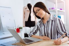 Happy female looking at screen of computer. Online conversation. Attractive woman bowing head while expressing positivity and holding pencil in left hand royalty free stock photography