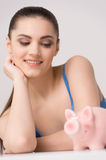 Happy female looking at table with piggy bank. Stock Photography