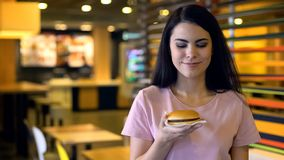 Happy female looking at tasty burger in hand, sandwich club, unhealthy nutrition royalty free stock image