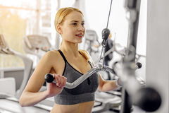 Happy female making exercise on triceps. Smiling woman working out with pulldown station in gym. She pumping hands Royalty Free Stock Photography