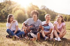 Happy female and male students enjoy picnic outdoor, sit grouped together, laugh and joke among themselves, sing songs to guitar,. Admire beautiful nature Stock Images