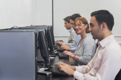 Happy female mature student sitting in computer class Royalty Free Stock Image