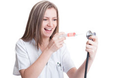 Happy female medic holding syringe and stethoscope Royalty Free Stock Photo