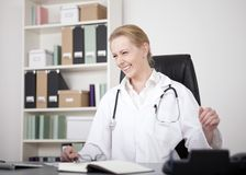 Happy Female Medical Doctor Sitting at her Office Royalty Free Stock Photos