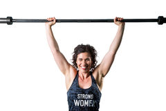 Happy Female Military Press. A happy and confident, muscular female trainer easily holds an unloaded barbell over her head. There is a isolation path stock image