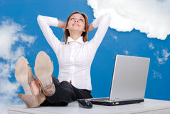 Happy female model with legs on desk. In sky Royalty Free Stock Image