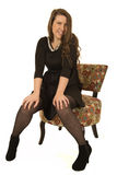 Happy female model sitting in a floral chair Royalty Free Stock Images