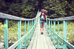 Happy female mountaineer standing on a wooden bridge over a mountain stream overflowing with excitement with the glory and beauty Stock Photo