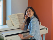 Happy female musician playing piano indoor royalty free stock images