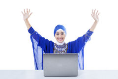 Happy female muslim and laptop - isolated. Happy female muslim in blue dress raised her arms with laptop on white Royalty Free Stock Photography