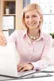 Happy female office worker with laptop computer Royalty Free Stock Image