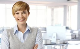 Happy female office worker. Portrait of happy female office worker at office, smiling. Copyspace Royalty Free Stock Images