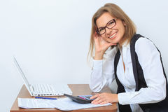 Happy female office worker sits at her desk and Stock Photography