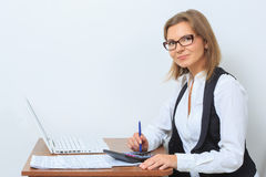 Happy female office worker sits at her desk and Royalty Free Stock Photography