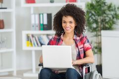 Happy female office worker in wheelchair holding laptop Royalty Free Stock Photo