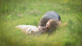 Happy female owner with her dog. She petting her labrador dog lying on the grass. Happy female owner with her dog. She petting her labrador, dog lying on the stock footage