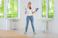 Happy female painter holding paintroller and color palette Royalty Free Stock Photo