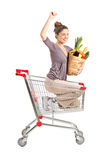 Happy female with a paper bag into a shopping. A view of a happy female with a paper bag posing into a shopping cart isolated on white background stock image