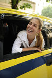 Happy female passenger inside of a taxi Royalty Free Stock Photo