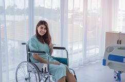 Happy female patient in hospital room. A portrait of happy female patient in hospital room with thumb up posture. She smiles to her doctor and nurse as she stock photography