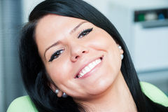 Happy female patient smiling after bleaching or whitening. In dental office royalty free stock photos